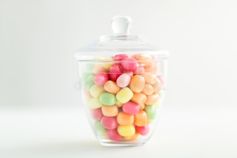 Tarro de cristal con gotas del caramelo sobre el fondo blanco fotografía de archivo