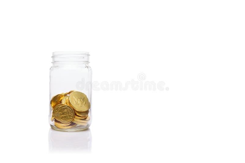 Tarro de cristal con la cantidad media de monedas de oro Nivel moderado de fotos de archivo libres de regalías