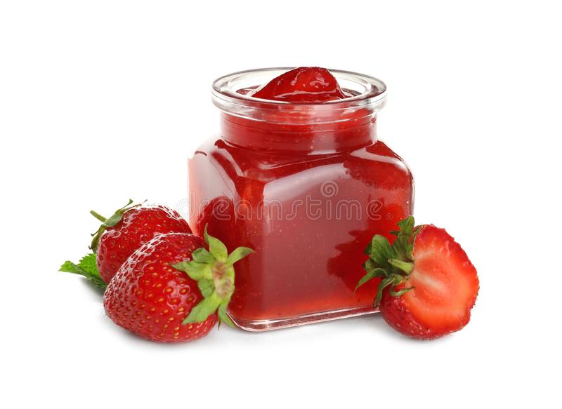 Tarro de cristal con la mermelada de fresa sabrosa en el fondo blanco imagen de archivo