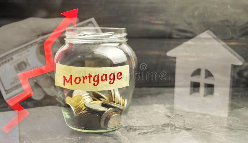 Tarro de cristal con las monedas y la inscripción 'hipoteca 'y para arriba flecha El aumento en tipos de interés en hipotecas Pré fotografía de archivo