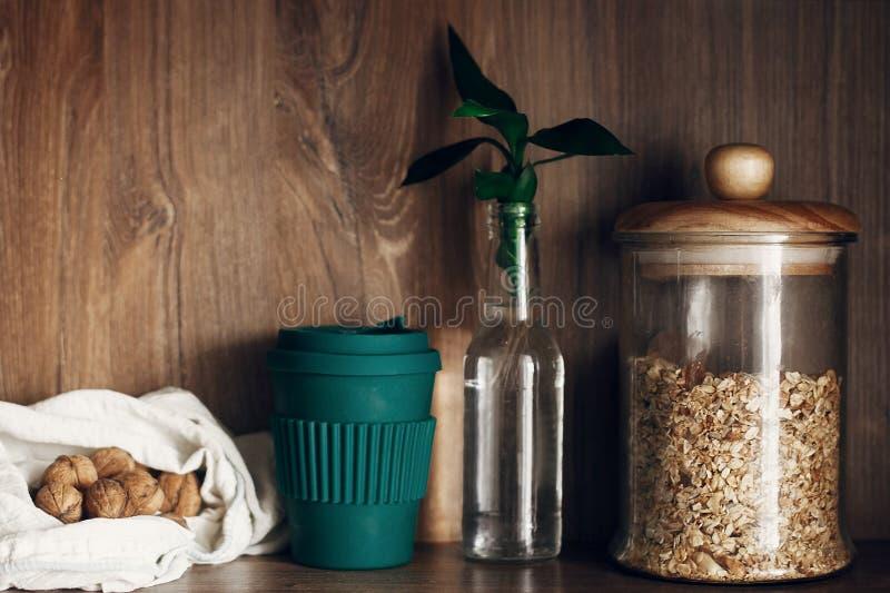 Tarro de cristal con los cereales, bolso que hace compras reutilizable con las nueces, hojas reutilizables del taza de café y de  imagen de archivo