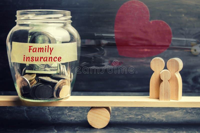 Tarro de cristal con seguro del dinero y de la familia de las palabras y la familia en las escalas El concepto de seguro médico d imagen de archivo libre de regalías