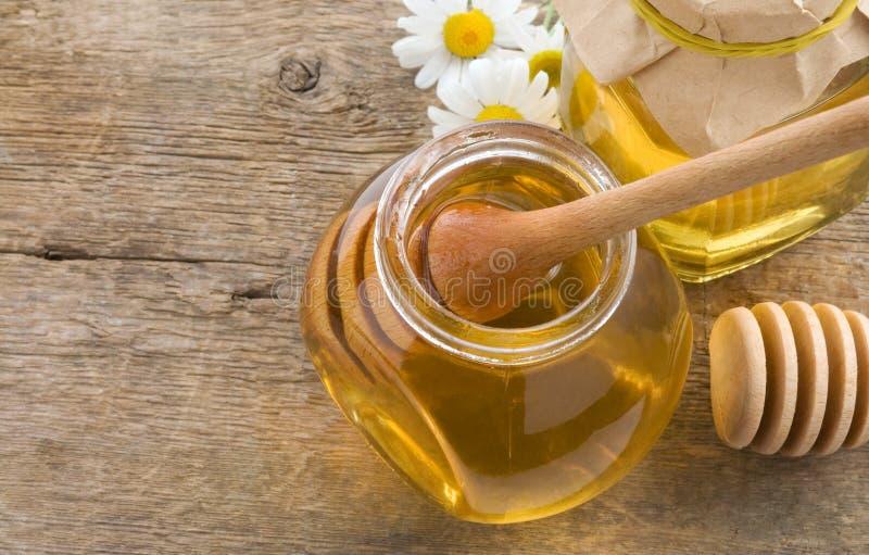 Tarro de cristal de la miel y del palillo en la madera foto de archivo