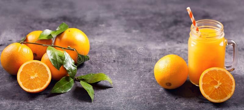 Tarro de cristal de zumo de naranja fresco con las frutas frescas fotografía de archivo libre de regalías