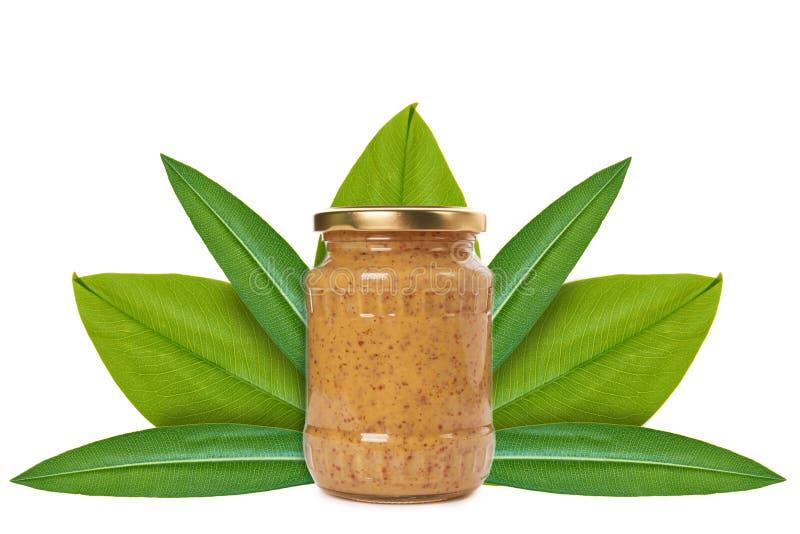 Tarro de cristal de mostaza en el fondo de hojas verdes Aislado en blanco noción del origen natural fotos de archivo libres de regalías