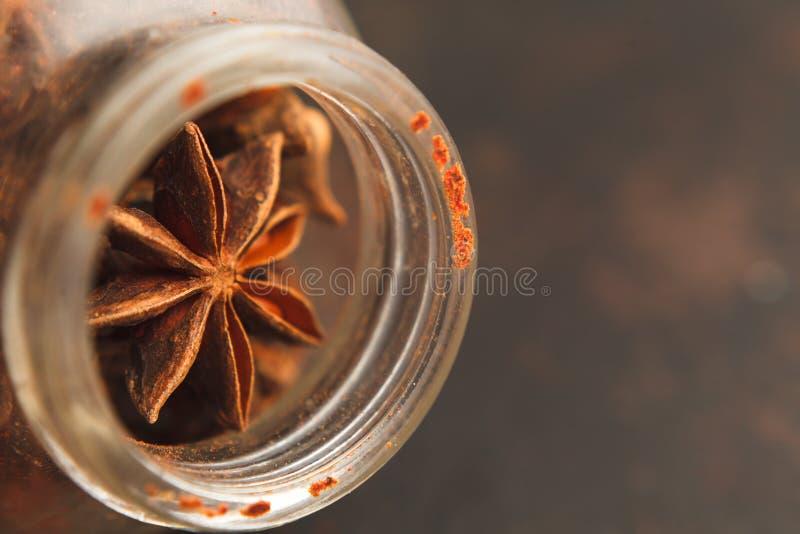Tarro de cristal viejo con las semillas del anís de estrella en un fondo oscuro imagenes de archivo