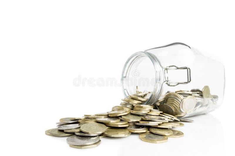 Tarro de cristal volcado con las monedas de oro y de plata aisladas en el fondo blanco imagen de archivo