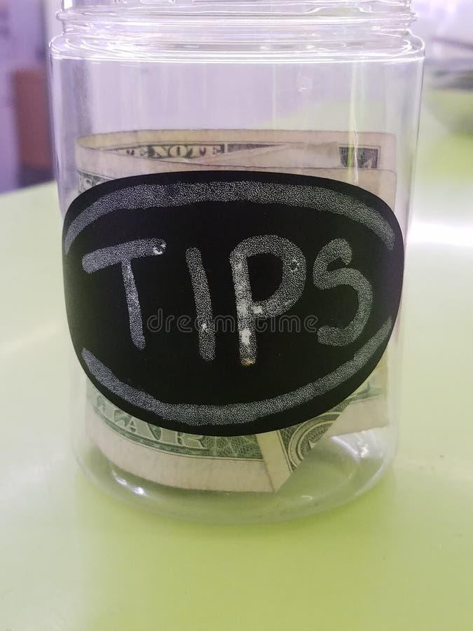 Tarro de la extremidad en café con el dinero dentro en contador del pago y envío imagenes de archivo