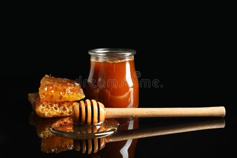 Tarro de la miel, del cazo de madera y del panal contra fondo oscuro imágenes de archivo libres de regalías