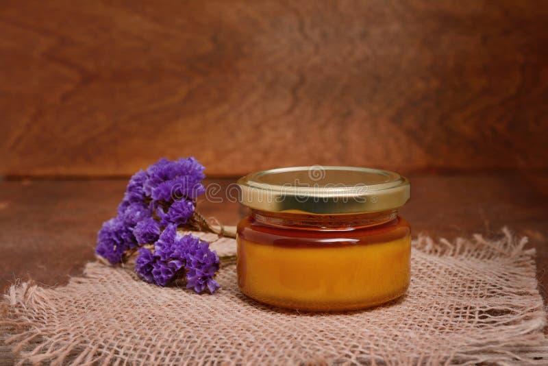 Tarro de la miel y de la rama de una lavanda en una tabla de madera con la tela áspera imagenes de archivo