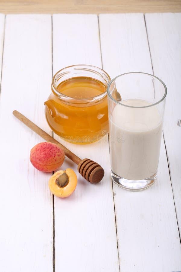 Tarro de miel y de un vidrio de leche en una tabla de madera foto de archivo libre de regalías