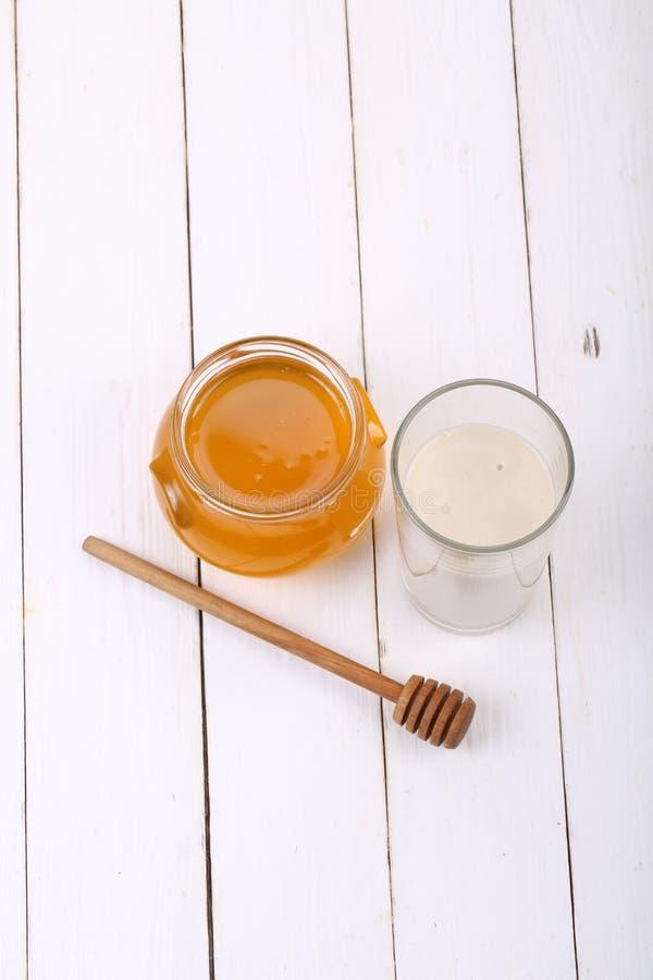 Tarro de miel y de un vidrio de leche en una tabla de madera imagenes de archivo