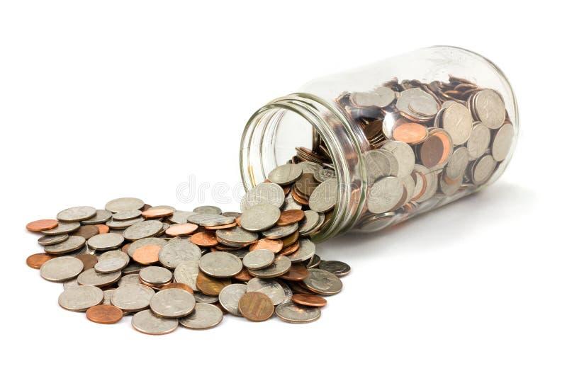Tarro de monedas derramadas en el fondo blanco foto de archivo libre de regalías