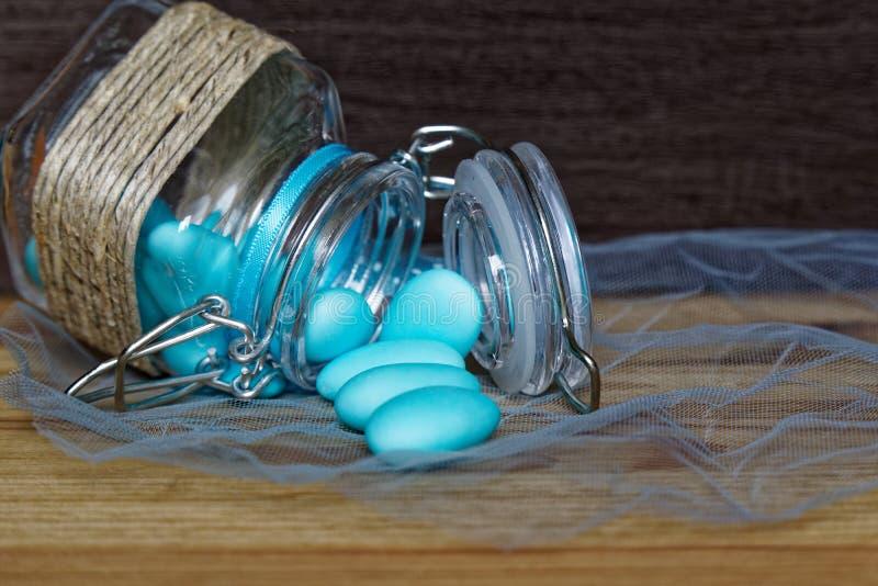 Tarro decorativo con el arco y las piedras azules dentro en la tabla de madera, maqueta para la postal o tarjeta de felicitación foto de archivo