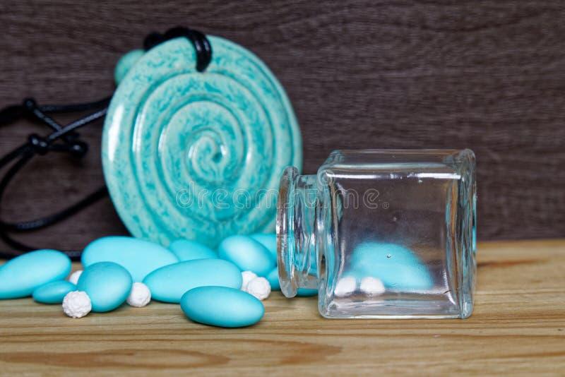 Tarro decorativo con el arco y las piedras azules dentro en la tabla de madera, maqueta para la postal o tarjeta de felicitación imagen de archivo