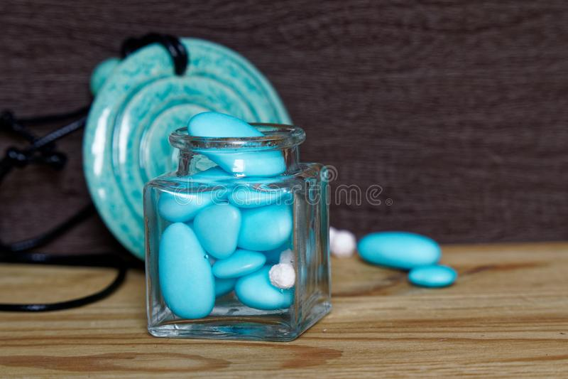 Tarro decorativo con el arco y las piedras azules dentro en la tabla de madera, maqueta para la postal o tarjeta de felicitación fotografía de archivo