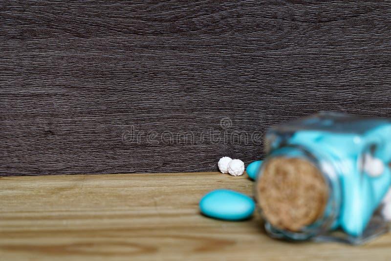 Tarro decorativo con el arco y las piedras azules dentro en la tabla de madera, maqueta para la postal o tarjeta de felicitación fotos de archivo