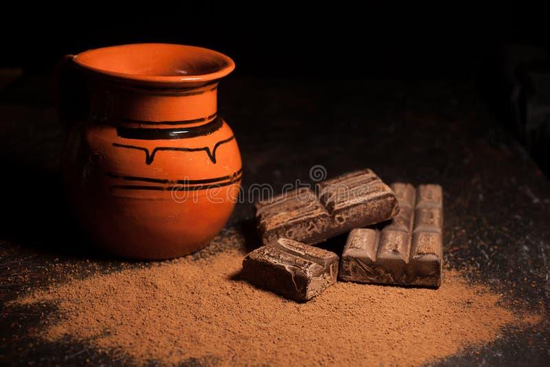 Tarro del chocolate caliente y de la barra de chocolates mexicana tradicional en fondo negro imagenes de archivo