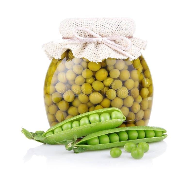 Tarro del guisante verde con las vainas frescas aisladas en blanco imagen de archivo