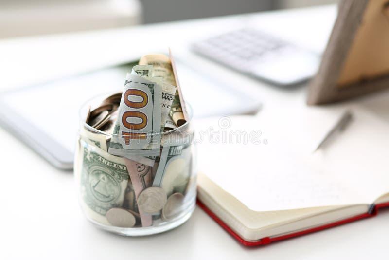 Tarro grande por completo de billetes y de monedas de los E.E.U.U. que se colocan en la mesa de trabajo vacía fotografía de archivo libre de regalías