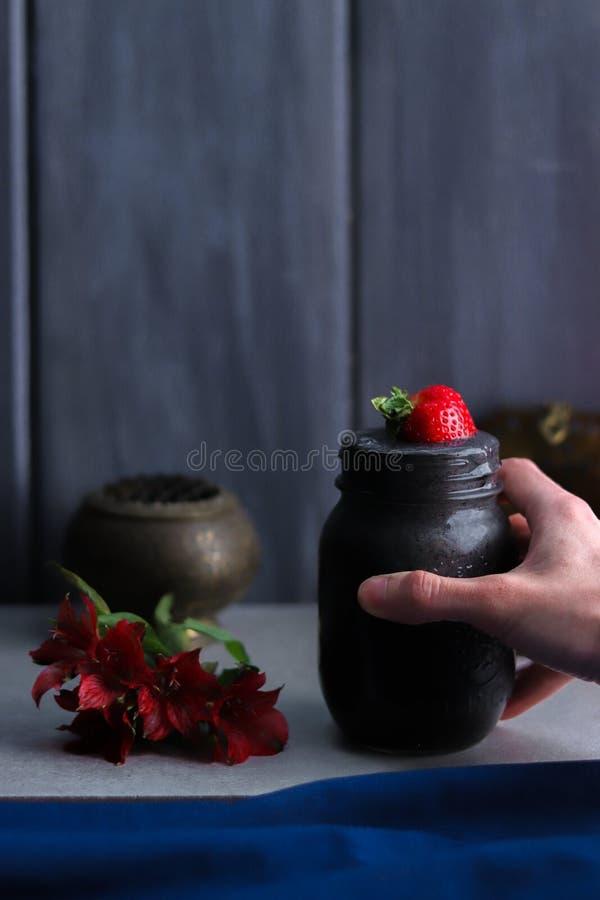 Tarro oscuro azul del Smoothie con la fresa y la mano imagen de archivo libre de regalías
