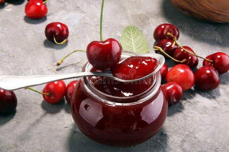 Tarro rústico con el atasco de cereza y las cerezas frescas, coto hecho en casa fotografía de archivo libre de regalías