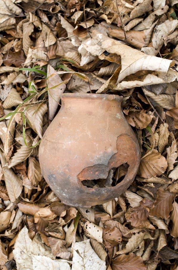 Tarro roto viejo en hojas de otoño secas fotos de archivo