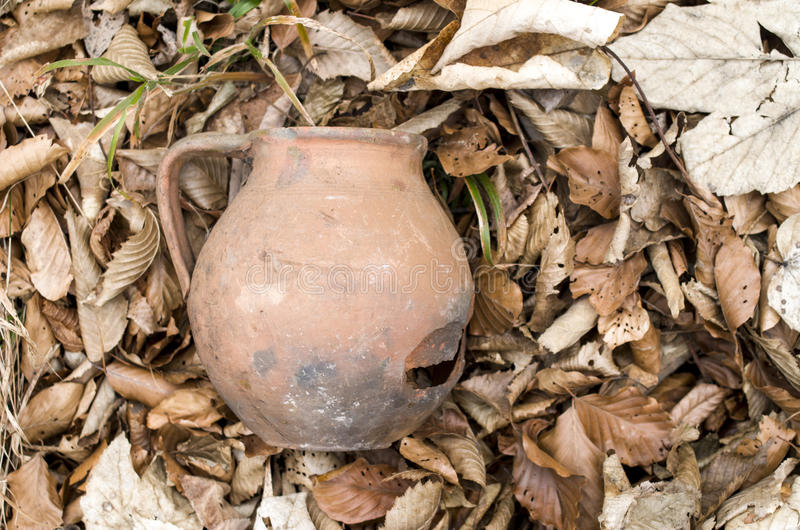 Tarro roto viejo en hojas de otoño secas foto de archivo