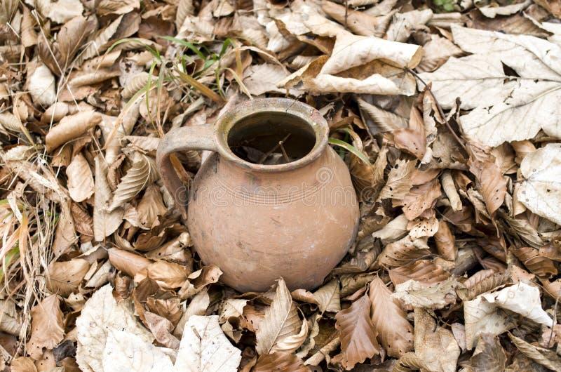 Tarro roto viejo en hojas de otoño secas foto de archivo libre de regalías