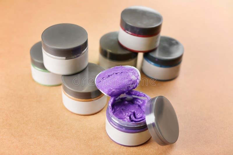Tarros con el material de coloración del cabello en la tabla imágenes de archivo libres de regalías