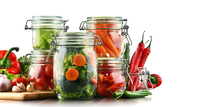 Tarros con la comida adobada y las verduras crudas aisladas en blanco imagenes de archivo