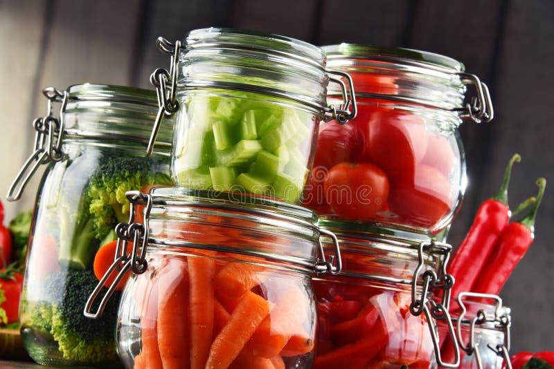 Tarros con la comida adobada y las verduras crudas orgánicas fotografía de archivo