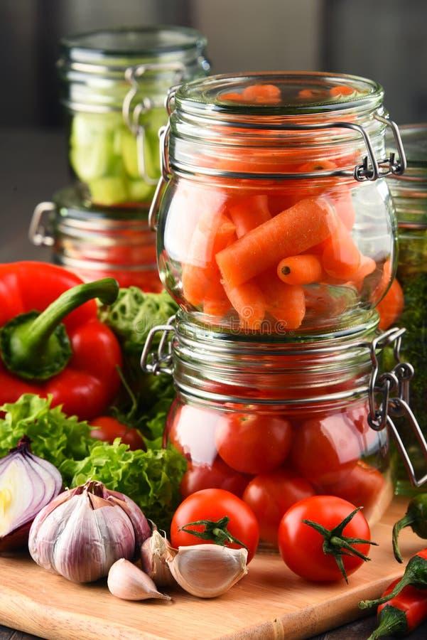 Tarros con la comida y las verduras crudas adobadas en tabla de cortar foto de archivo libre de regalías