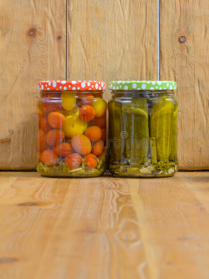 Tarros con las diversas verduras conservadas en vinagre Pepinos y tomates conservados imagen de archivo libre de regalías