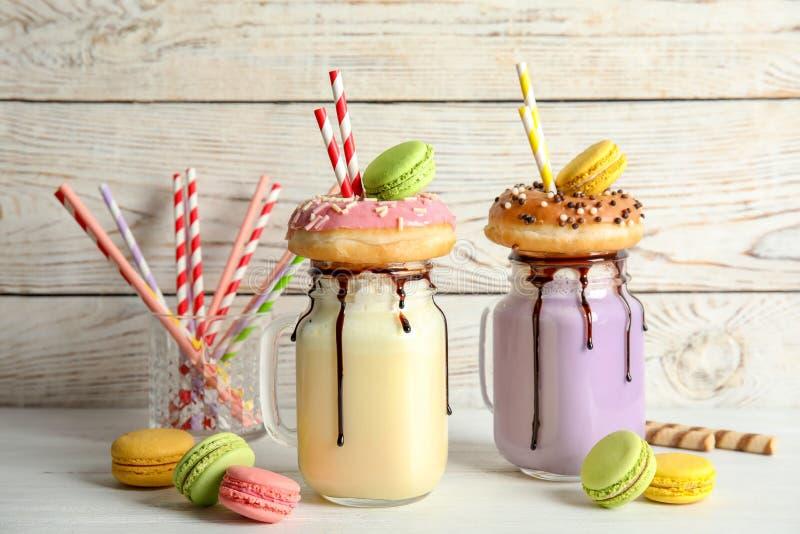 Tarros de albañil con batidos y macarrones de leche deliciosos fotografía de archivo