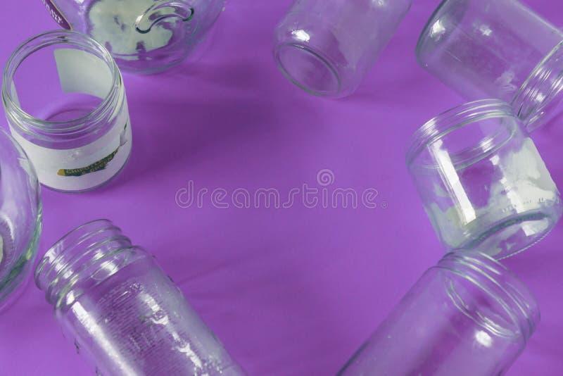 Tarros de cristal aislados, ningunas tapas completamente, fondo púrpura violeta, sitio del espacio de la copia fotos de archivo libres de regalías