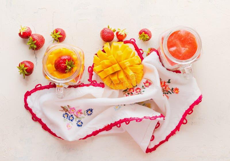 Tarros de cristal con las fresas y los smoothies del mango en el fondo blanco de la tabla, visión superior Las frutas y las bayas foto de archivo