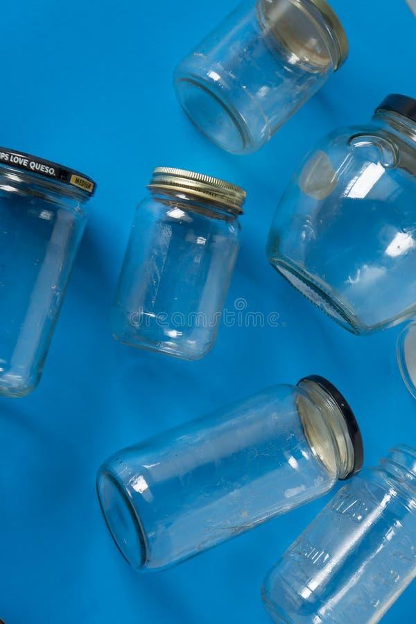 Tarros de cristal con las tapas en el fondo azul, endecha del plano de la visión superior que recicla concepto foto de archivo