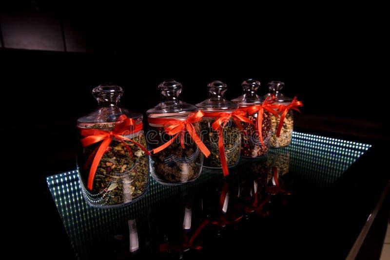 Tarros de cristal con los arcos rojos los cuales se completa el té foto de archivo libre de regalías