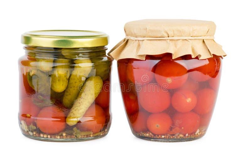 Tarros de cristal con los tomates y los pepinos adobados imágenes de archivo libres de regalías