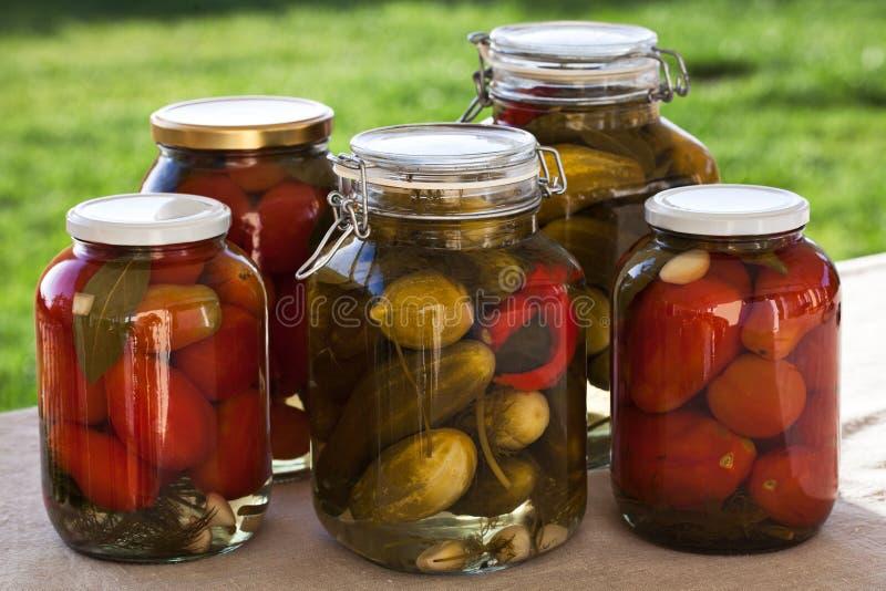 Tarros de cristal de tomates y de pepinos hechos en casa imagen de archivo libre de regalías