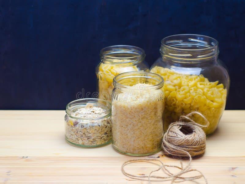 Tarros de cristal de empaquetado naturales para los productos a granel de las pastas, pensamientos, foco selectivo del arroz imagenes de archivo