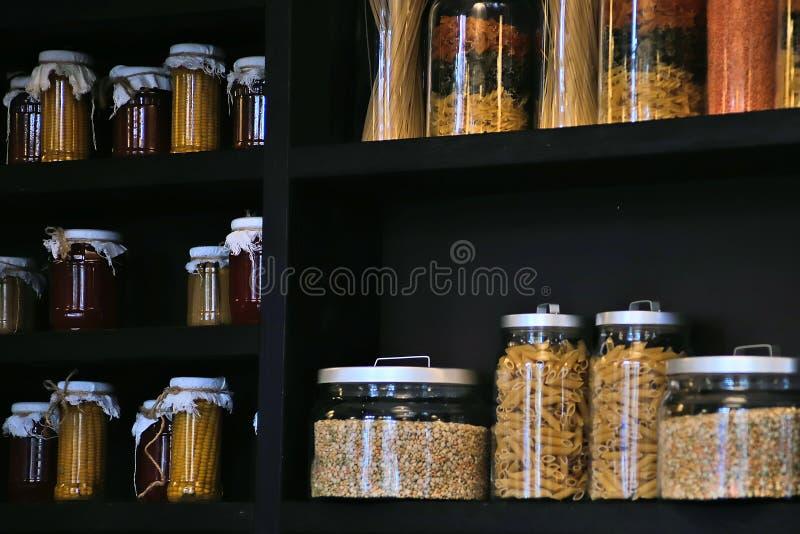 Tarros de cristal de la cocina hermosa para almacenar productos a granel en un estante oscuro con los cereales, las pastas, las e fotografía de archivo