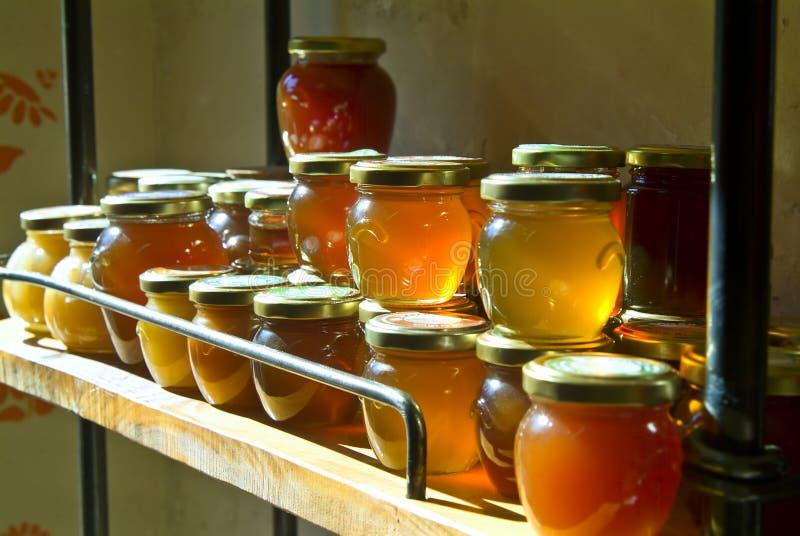 Tarros de la miel en un estante fotos de archivo