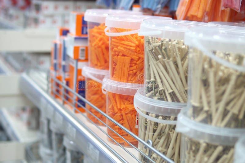 Tarros plásticos con los enchufes de la fijación y pasador-clavos en el estante de la tienda imagen de archivo libre de regalías