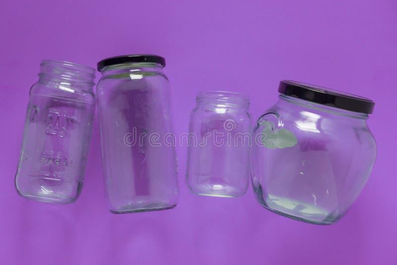 Tarros, plano y centro de cristal aislados en el fondo púrpura violeta - reciclando fotografía de archivo libre de regalías