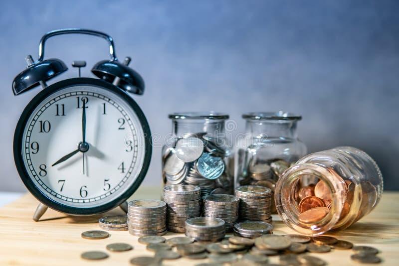 Tarros y reloj de la moneda Dinero del ahorro para el retiro imagen de archivo libre de regalías