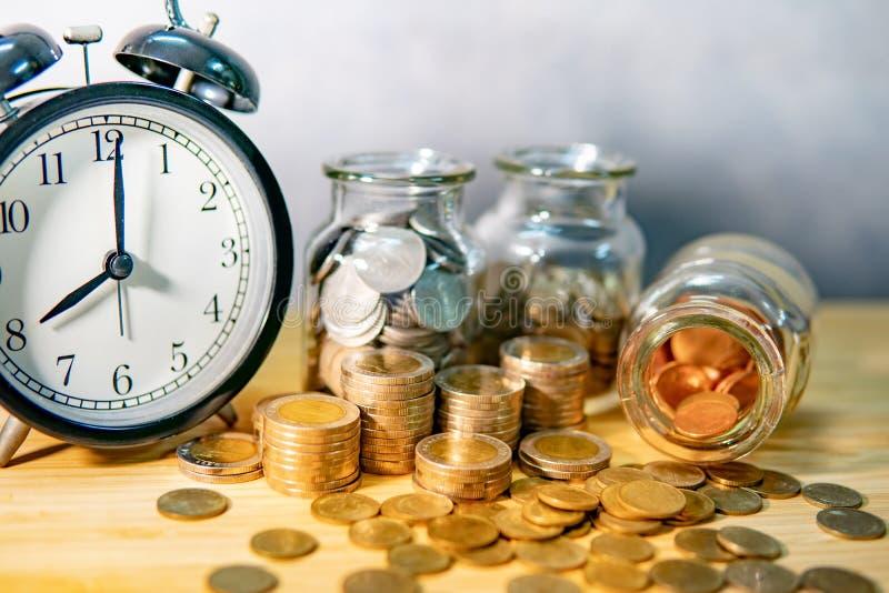 Tarros y reloj de la moneda Dinero del ahorro para el retiro foto de archivo