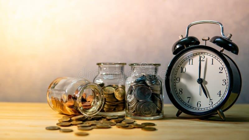 Tarros y reloj de la moneda Dinero del ahorro para el retiro imágenes de archivo libres de regalías