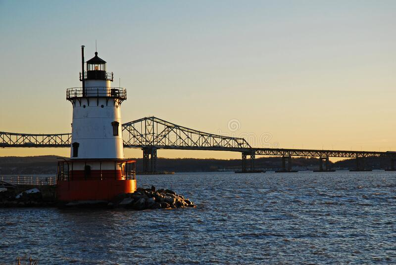 Tarrytown Lighthouse and old Tappan Zee Bridge. Tarrytown Lighthouse stands on the edge of the Hudson River with the old Tappan Zee Bridge in the background stock photography